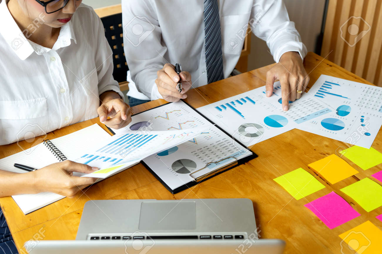 Business men and women are having a business plan consultation meeting by bringing information and graphs to study by putting notepads on the table to prepare to write idea - 169229530