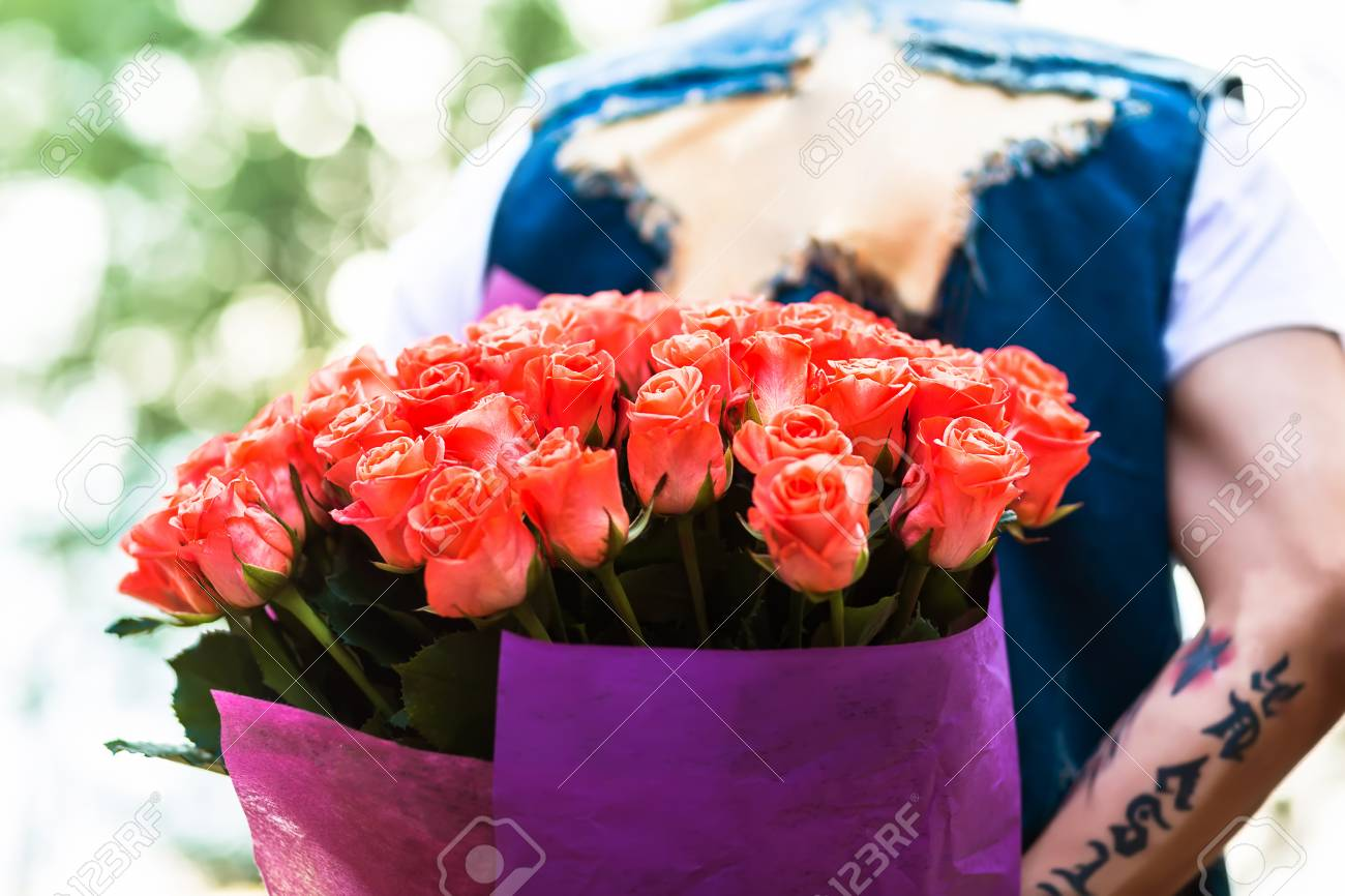Valentines day man hiding behind a bouquet of flowers bouquet man hiding behind a bouquet of flowers bouquet of roses behind of male izmirmasajfo Image collections