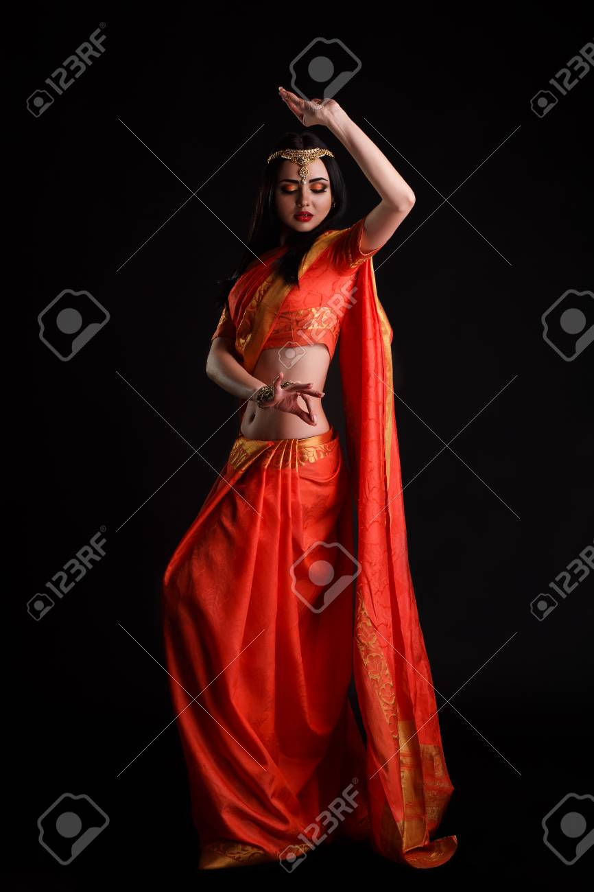 Happy young indian woman in sari dancing on black background. - 74766761