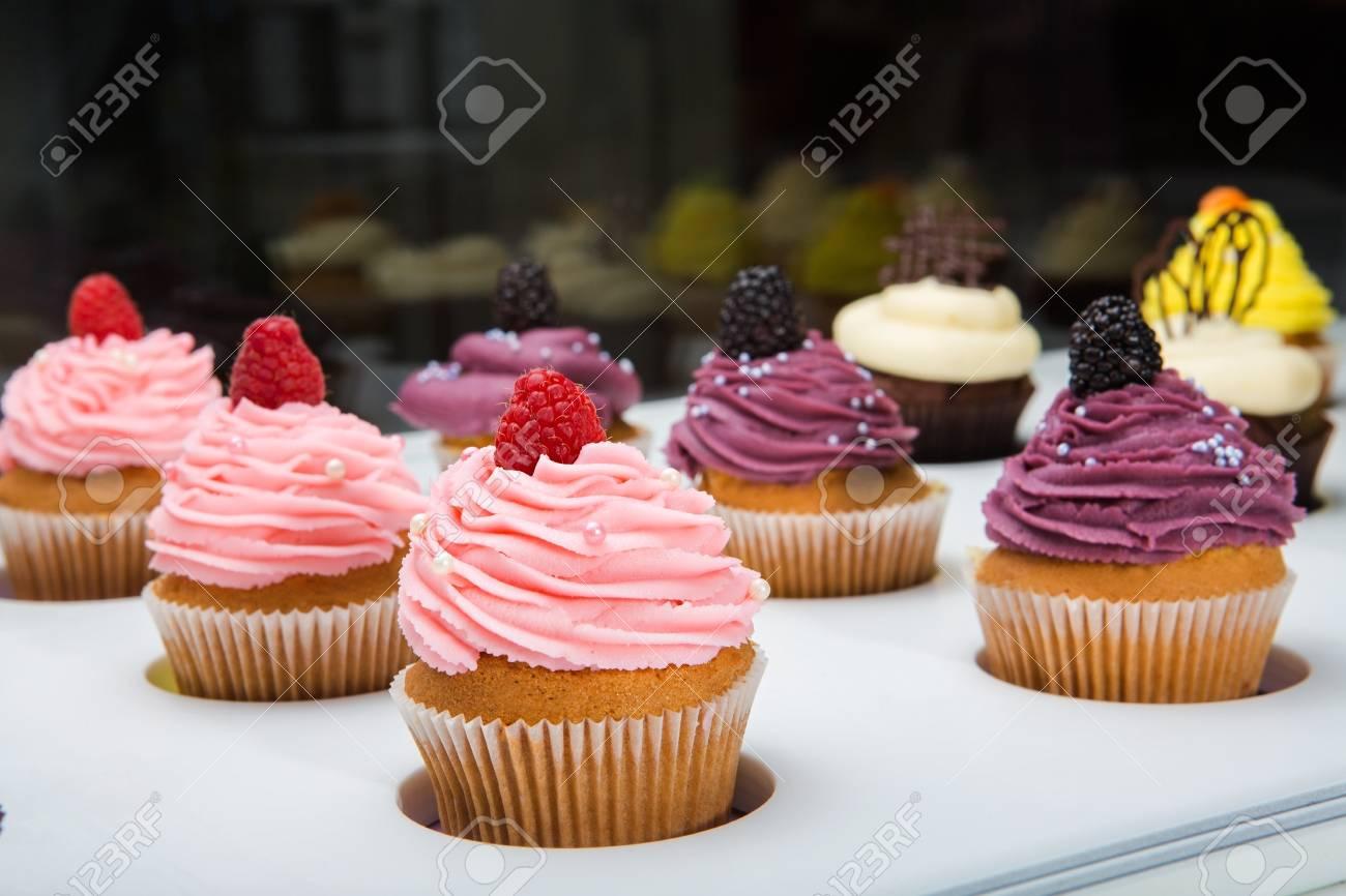 Bunte Cupcakes Mit Verschiedenen Geschmäcken. Kleine Schöne Kuchen Auf Die  Weiße Tischplatte. Standard