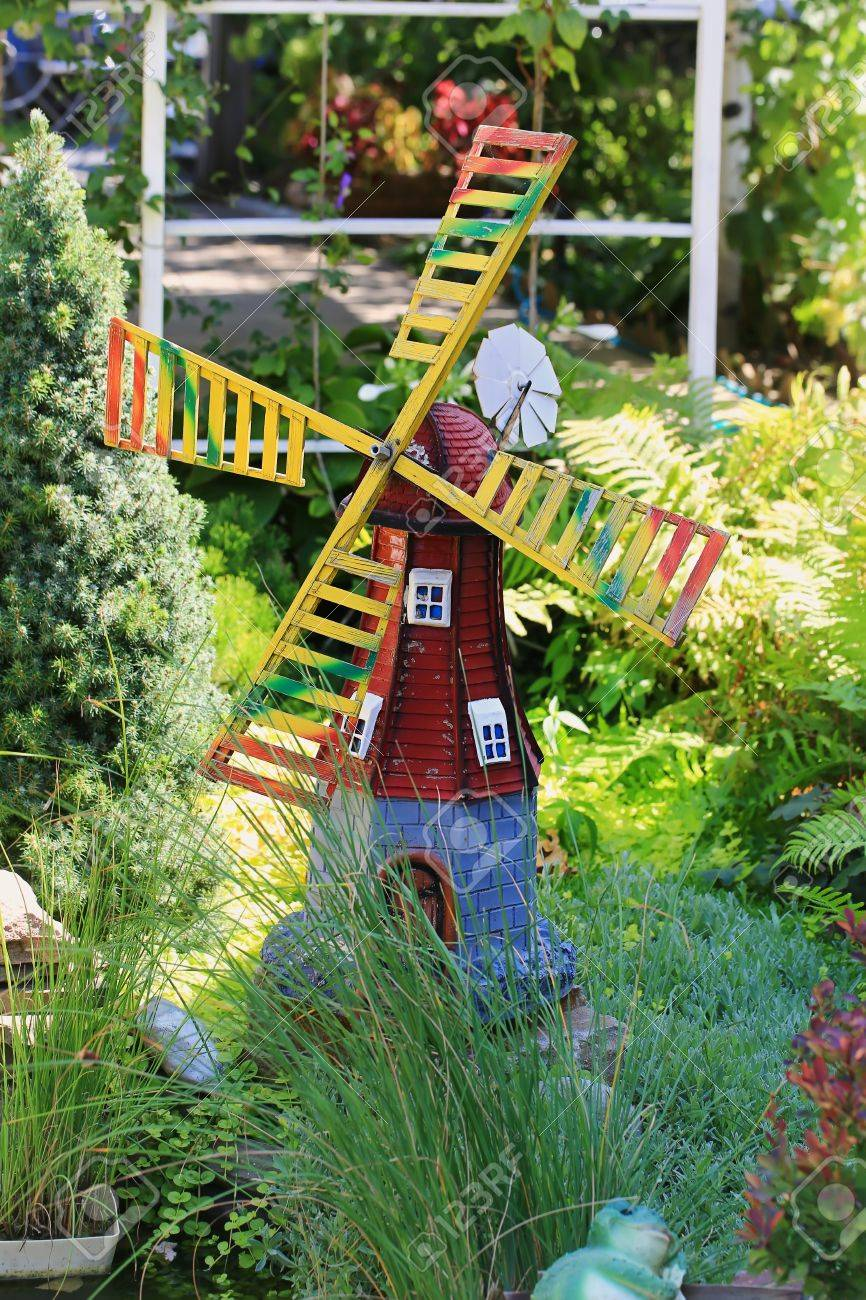 home garden decor figure wooden windmill in green grass summer..