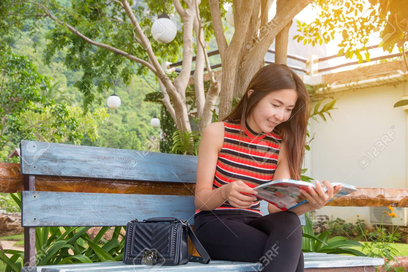 Beautiful Young Woman Sitting Read Book With Bag In Nature Free