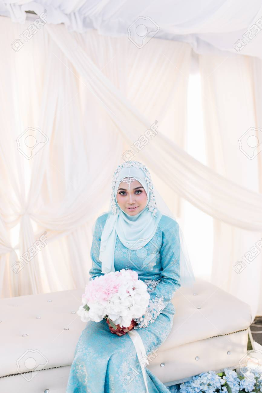 Portrait of Malaysian Muslim woman in wedding dress sitting and..