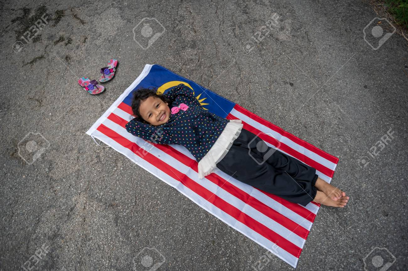 Cute Young Girl Lay On Malaysia Flag With Smile Merdeka Independence Day Theme
