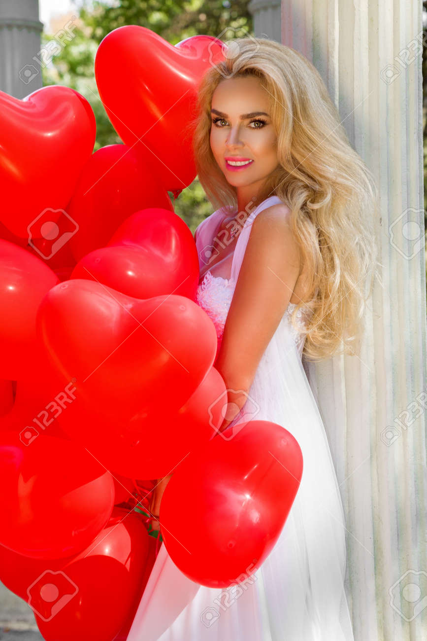 Bride in a wedding dress is walking in a beautiful garden and holding red balloons. Set of Air Balloons. Wedding fashion. Valentines day and bride at the wedding party. - 165753534