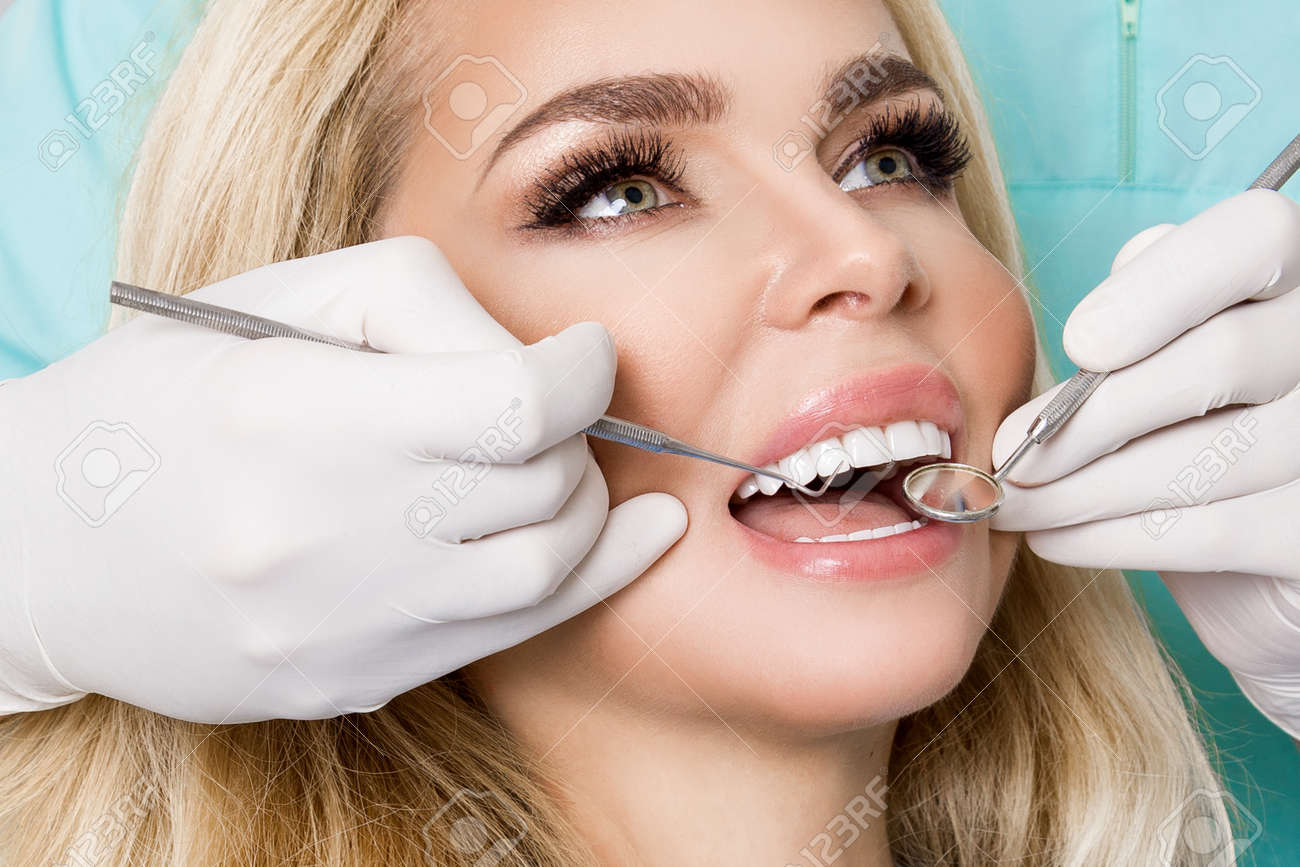 Porcelain veneers. Pretty female model with perfect smile. Young beautiful woman with beautiful white teeth sitting on a dental chair. Teeth whitening. - 165843940