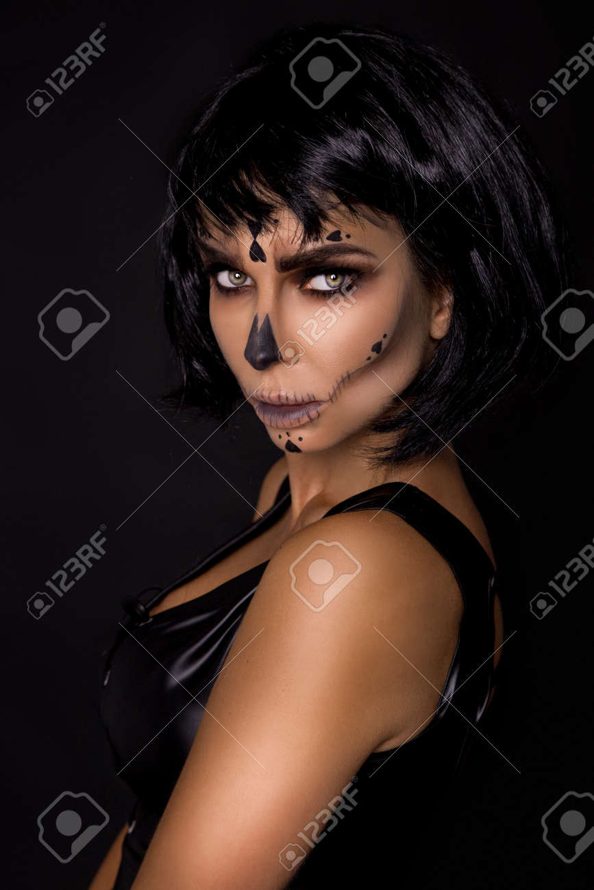 Portrait brunette woman in Halloween makeup on a black background in the studio. Makeup as skeleton, monster and witch. Halloween makeup. - 167234892
