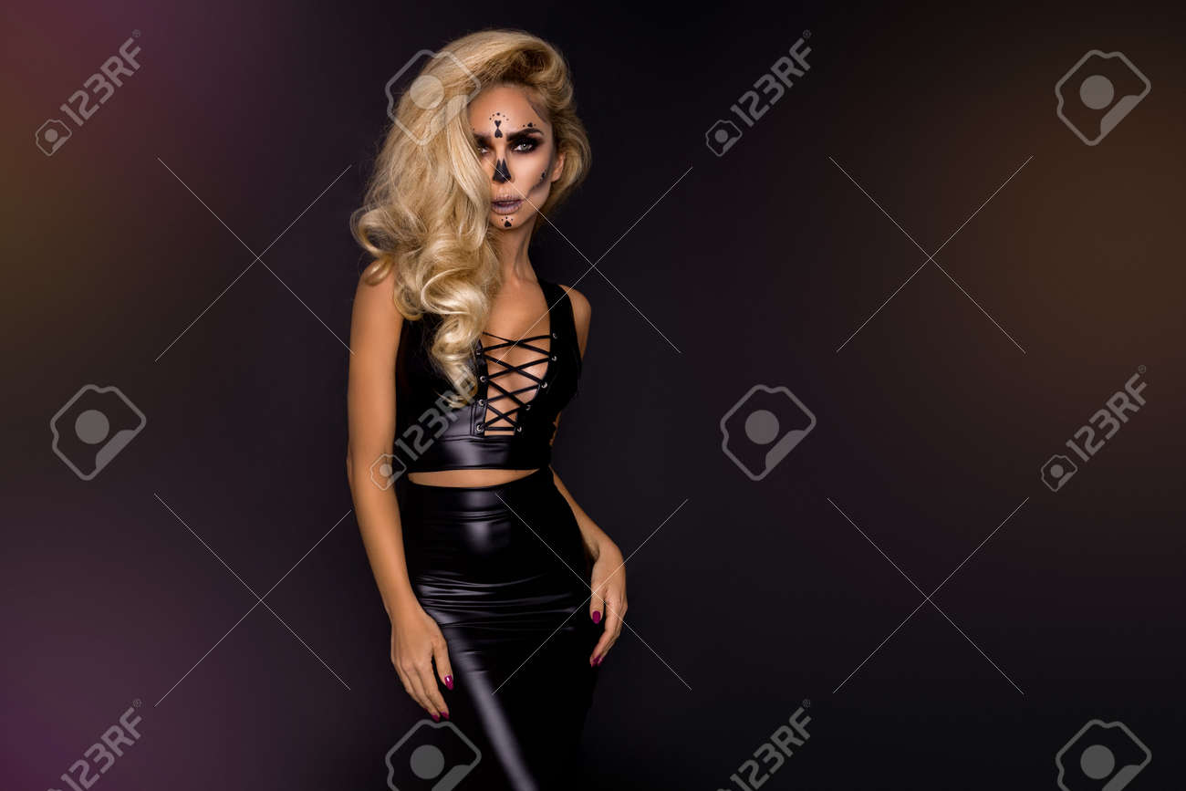 Sexy blonde woman in Halloween makeup and latex costume on a black background in the studio. Halloween makeup and costume. Sexy witch. - 167186132