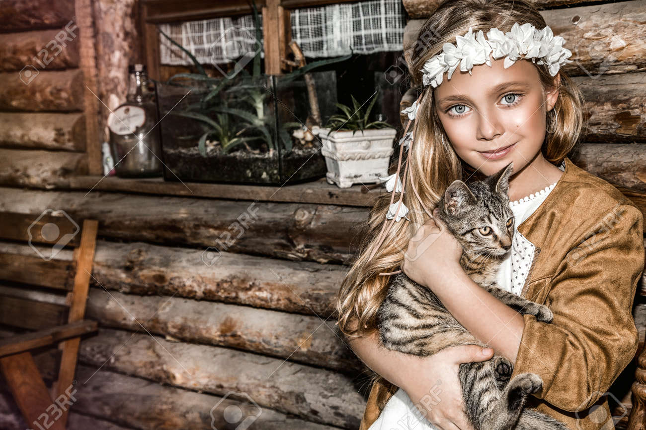Portrait of a small cute child with tenderness and love a cat and smiles with happiness. Little girl relaxing on park with her kitten. Child in white communion dress is kissing a cat. Spring fashion - 168854453