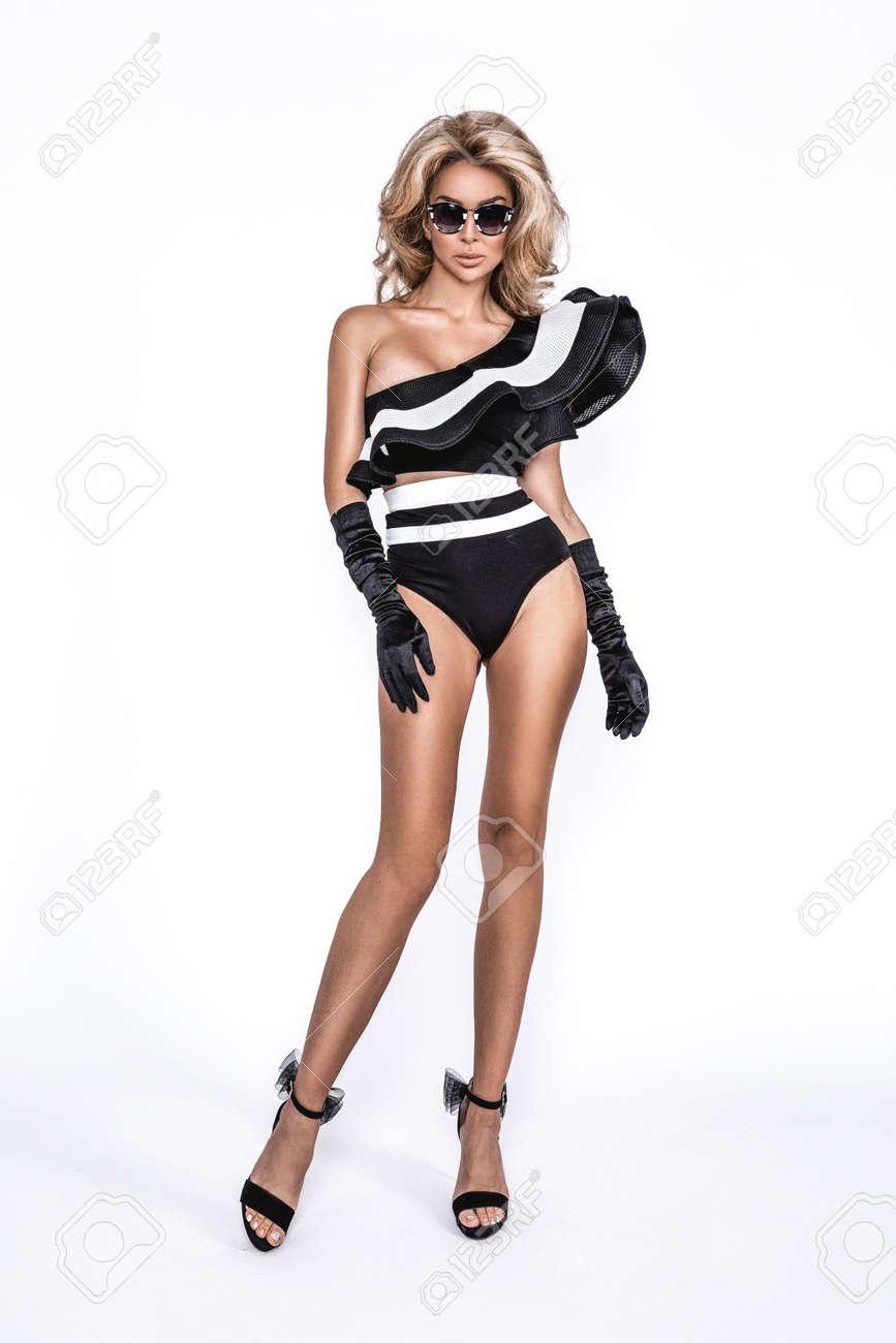 Bikini fashion. Elegant tanned woman in a black and white bikini and sunglasses isolated on white background in studio. Swimsuit fashion. Elegance. Summer fashion. - 169089660