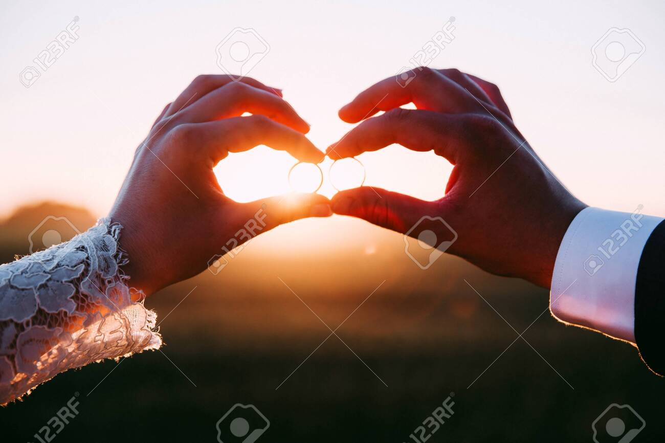 Two married people holding wedding rings at sunset. - 121889674