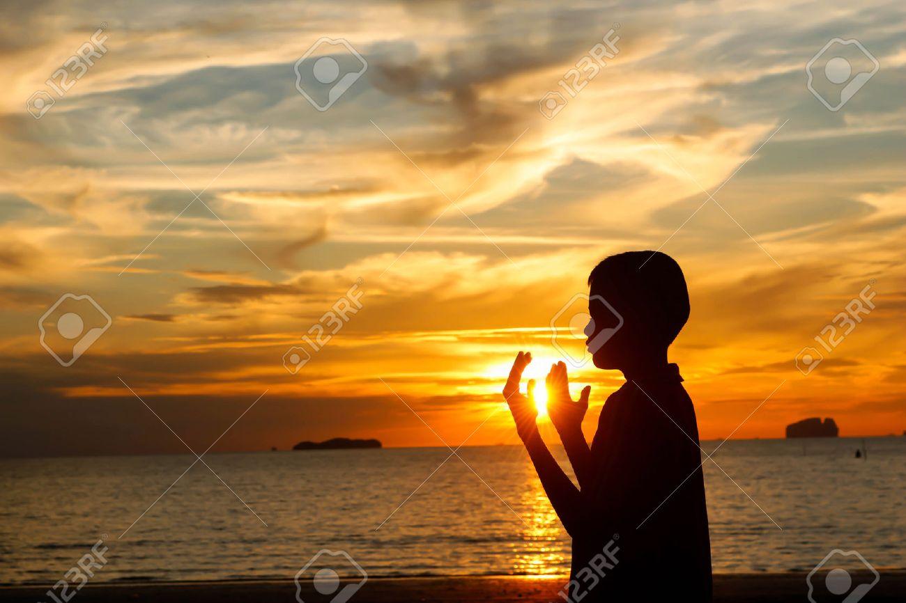 boy praying at sunset on the beach. - 52403244