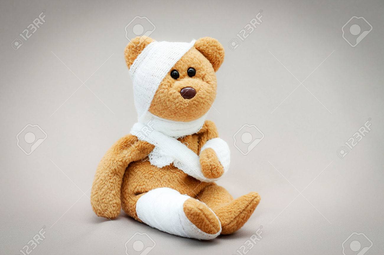 Teddy bear with bandage on gray background. - 62138187
