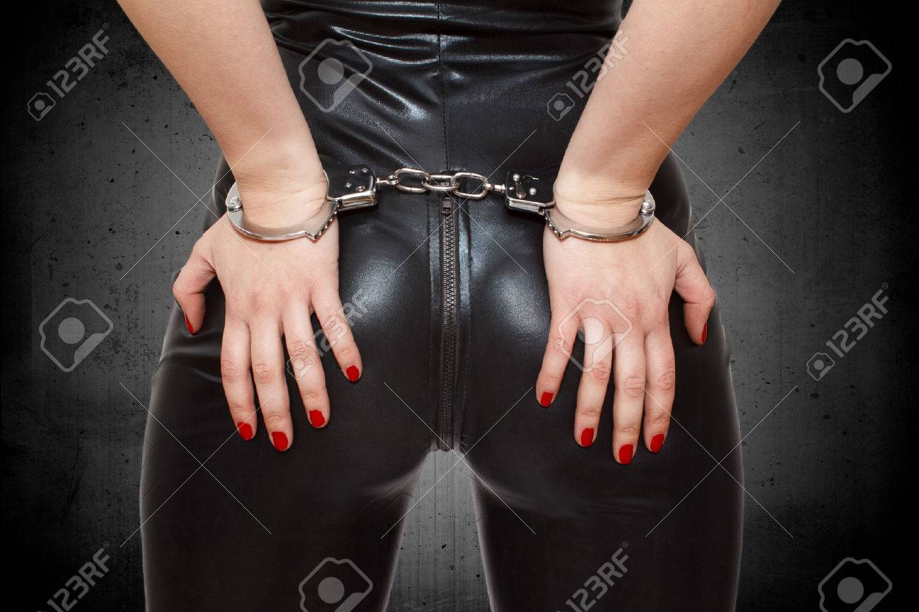 Sexy dominatrix, hands on ass in handcuffs, closeup Stock Photo - 25627429