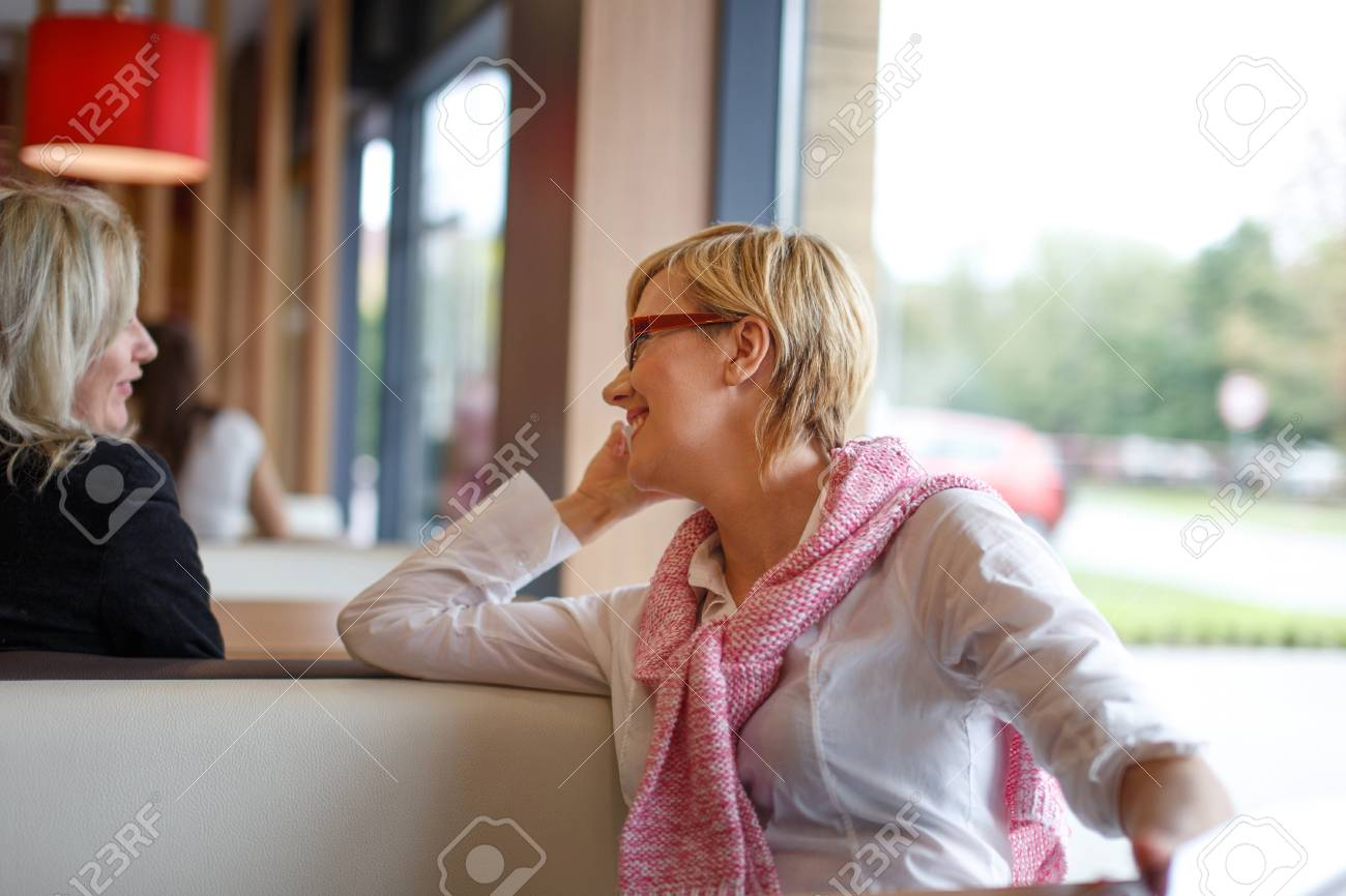 Young adult women chat and call in restaurant during coffee