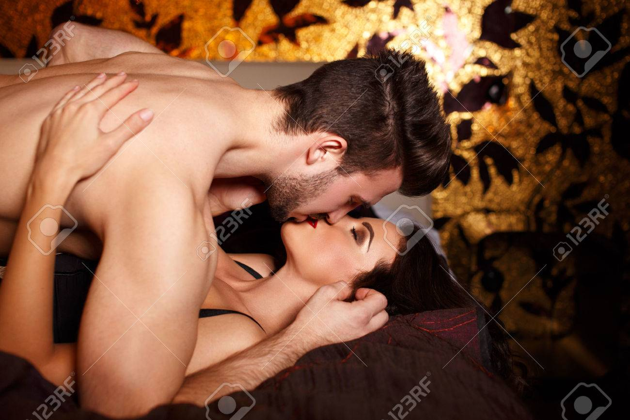 sexy couple kissing in bed at night, milf with young lover stock