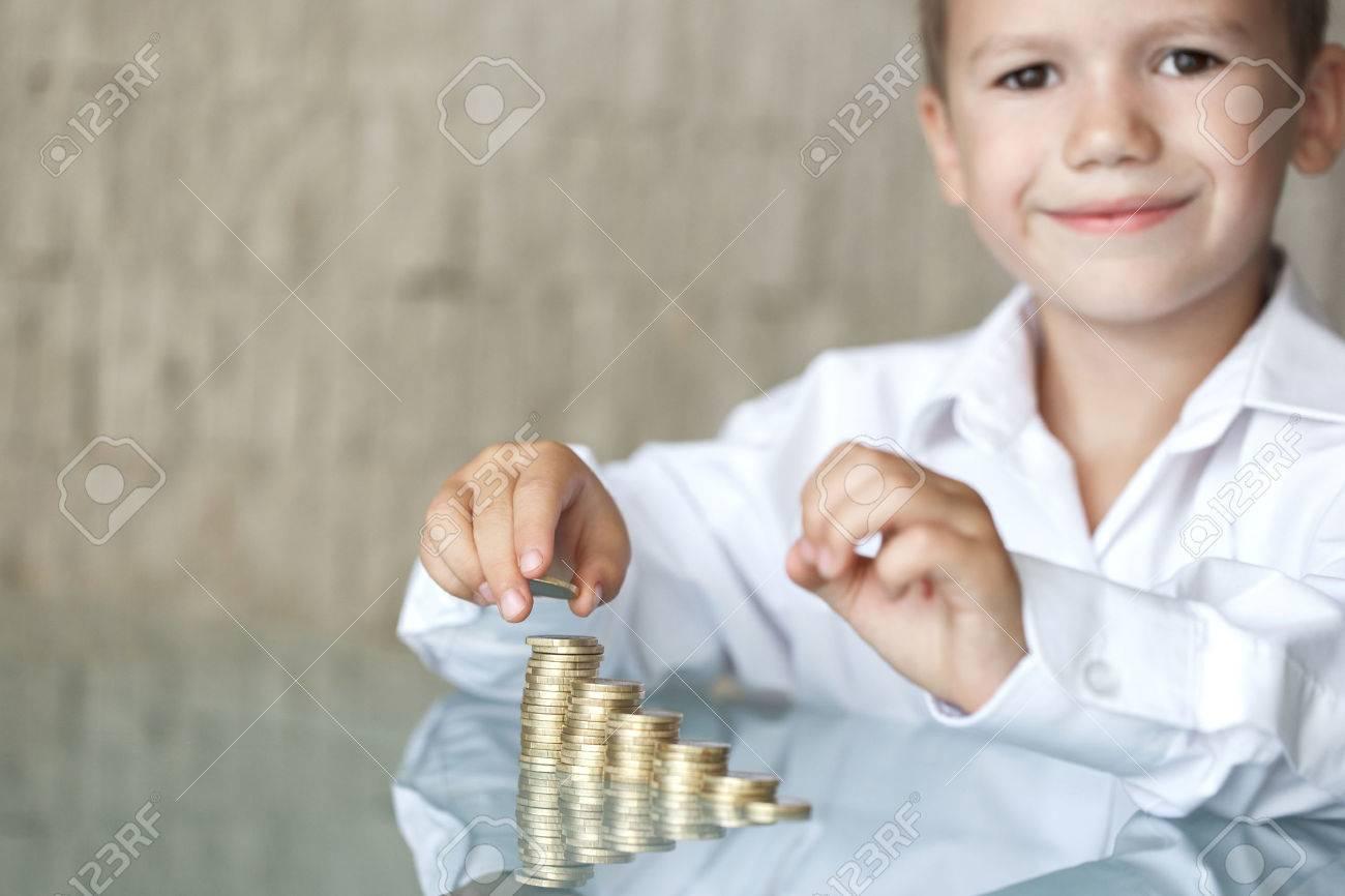 Petit garçon avec la colonne de pièces de monnaie sur le bureau de