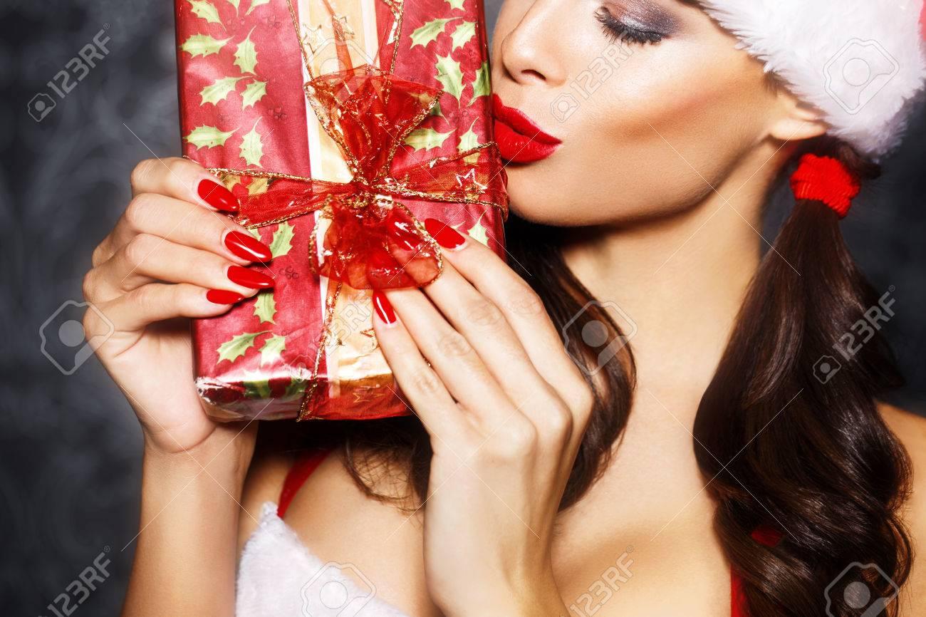 Sexy santa woman kissing gift closeup, red lips - 48425738