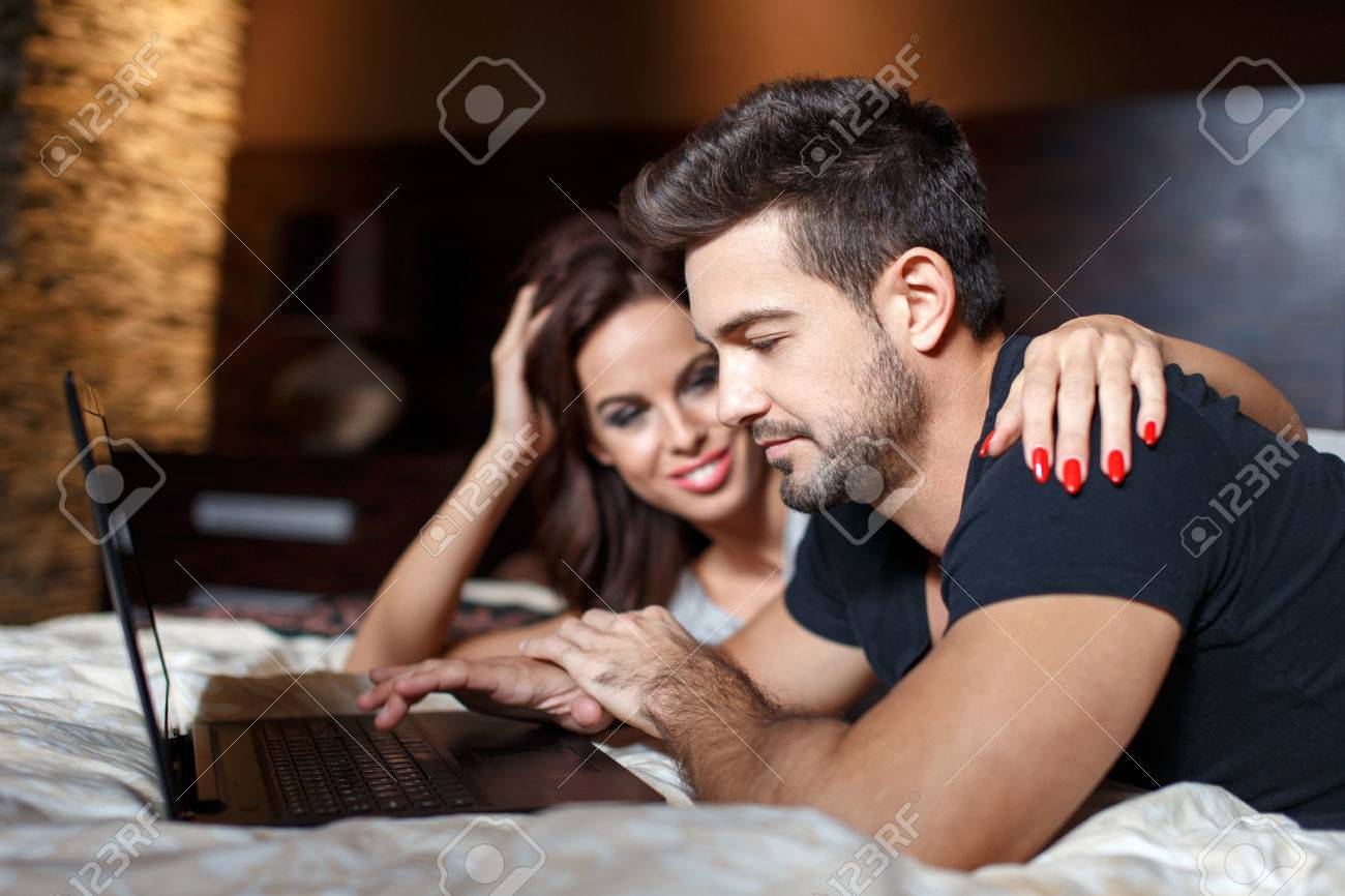 Young couple online shopping on bed by laptop, woman embrace man shoulder Stock Photo - 49644623