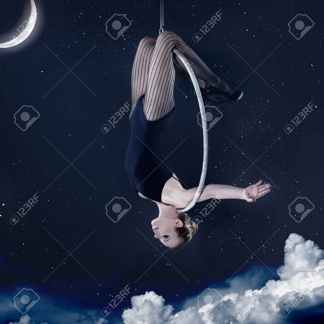 60bf8da4181e6 Woman hanging upside-down on aerial hoop at night over clouds,..