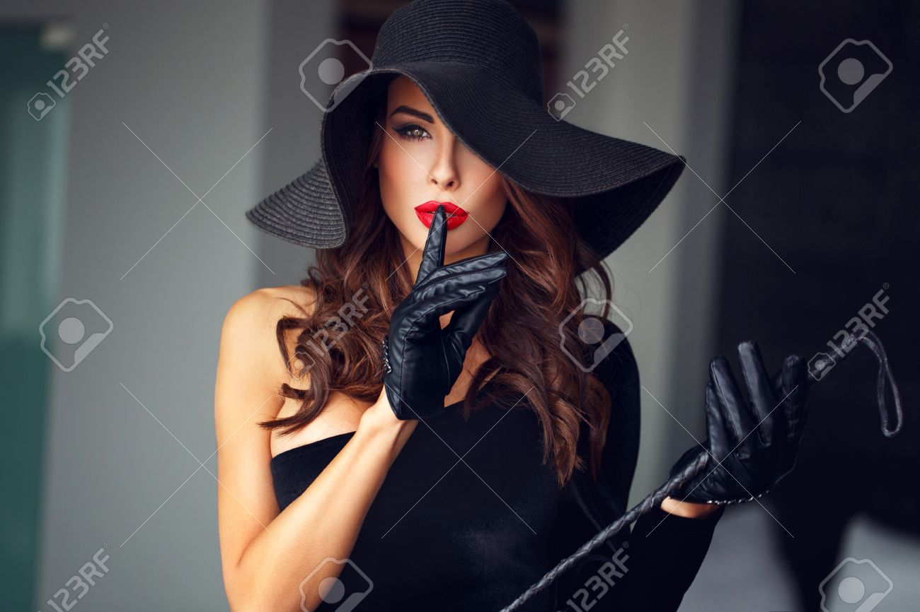 Sexy dominant woman in hat and whip showing no talk, - 52814340