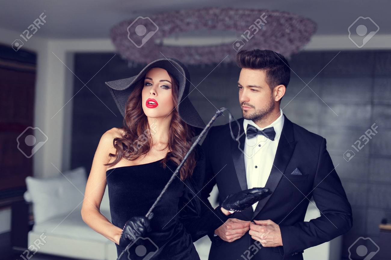 Sexy dominatrix woman posing with whip and young macho lover in tux - 55303622