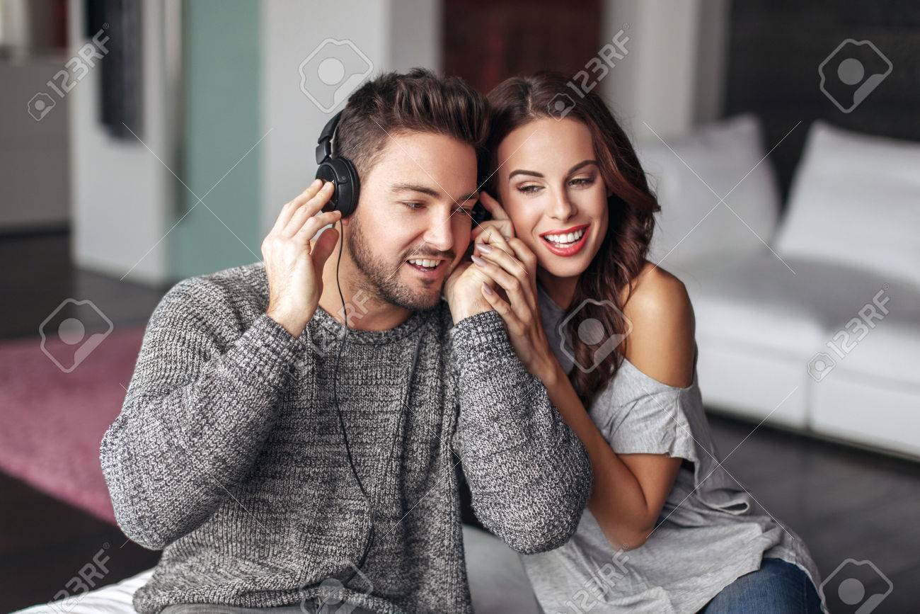 Happy young couple listening music and at home, sharing headphones - 58295721