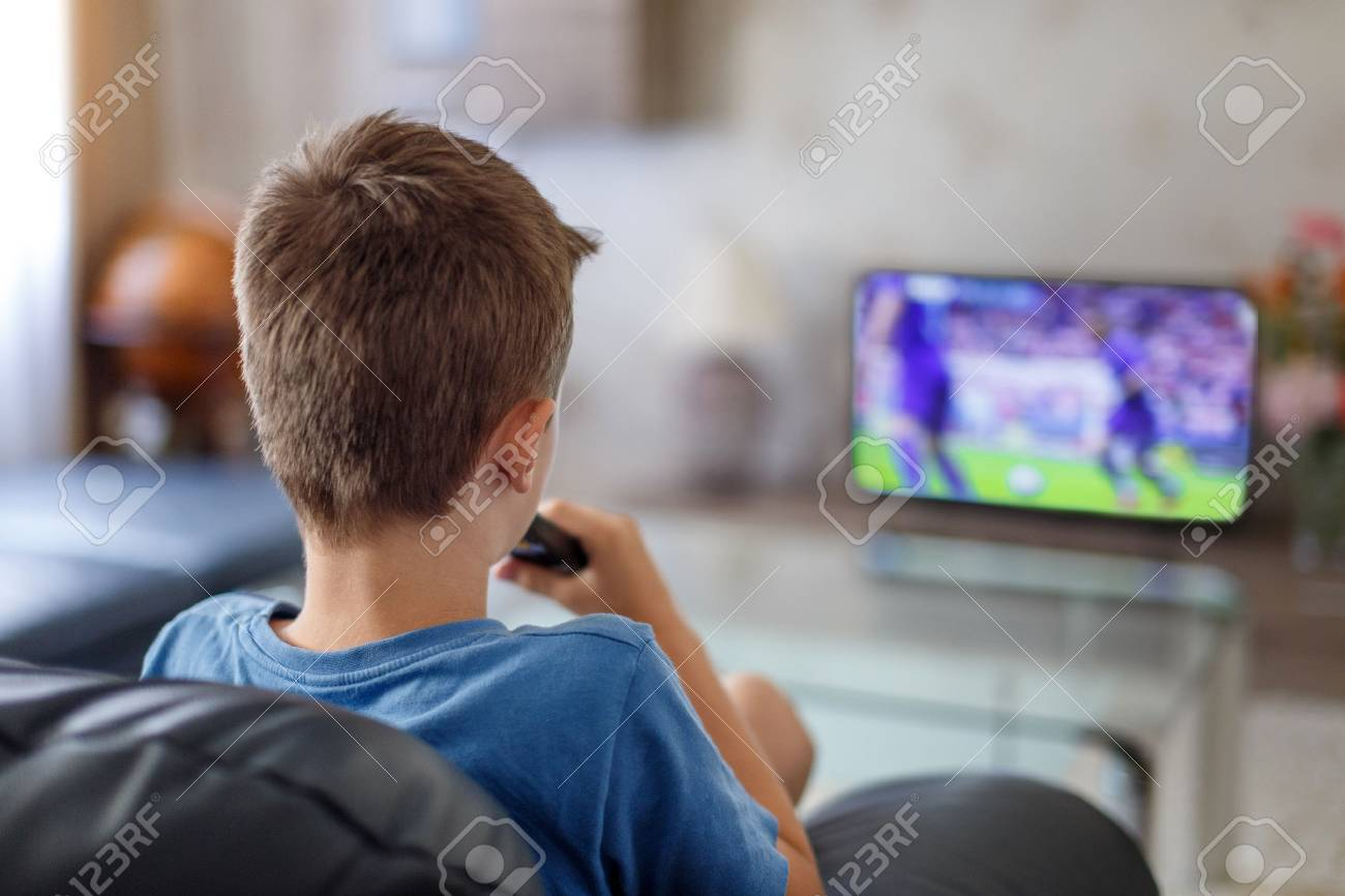 Excited little kid watching soccer match in TV at home - 59792998