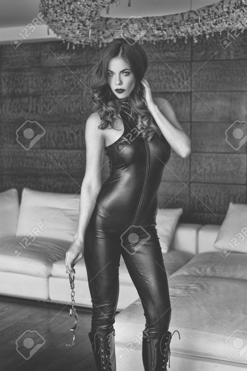 Sexy dominatrix in latex catsuit holding handcuffs, black and white, bdsm  Stock Photo -