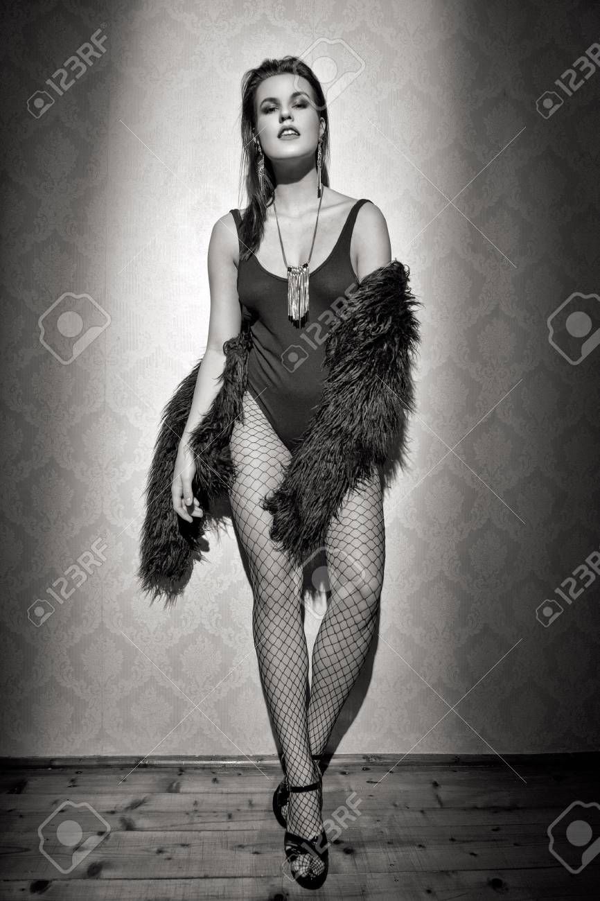 Fashionable sexy woman posing at vintage wall black and white stock photo 72579270