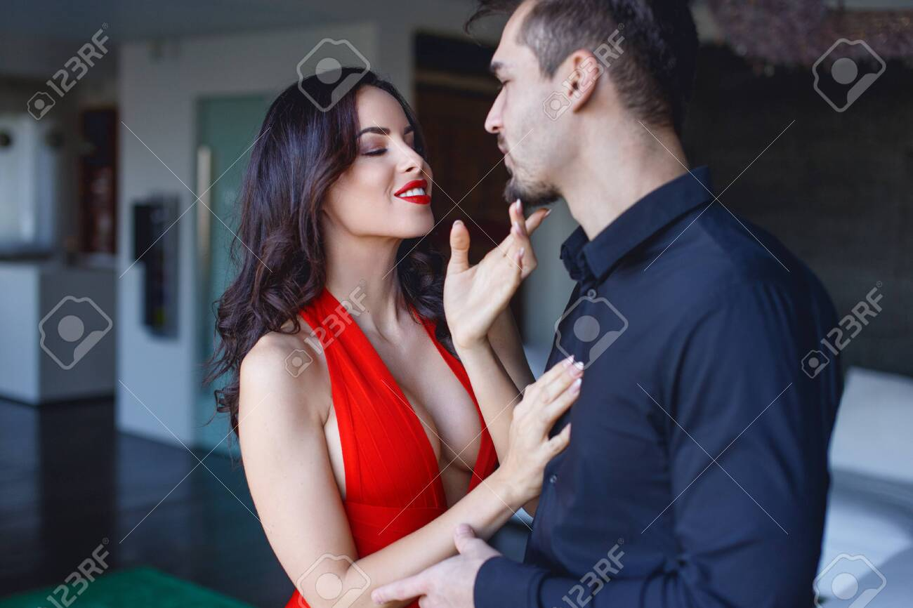 Sexy playful woman in red seducing younger man indoors - 151431314