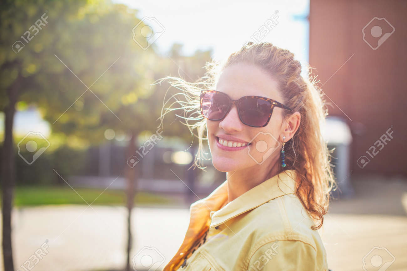 Young positive woman looking back with toothy smile at outdoors in park - 172341393