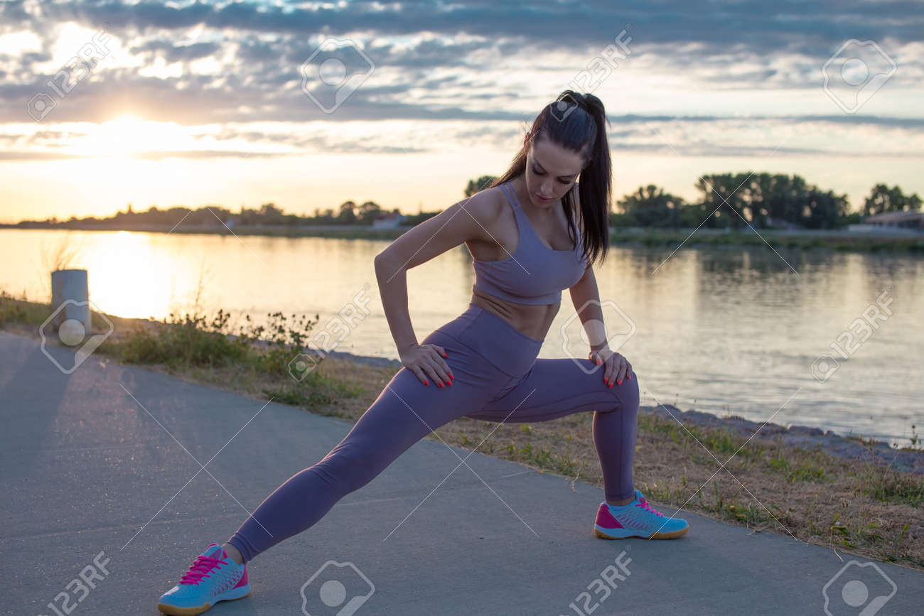 Young Caucasian woman stretching before running, warm up exercise in sunrise - 172324010