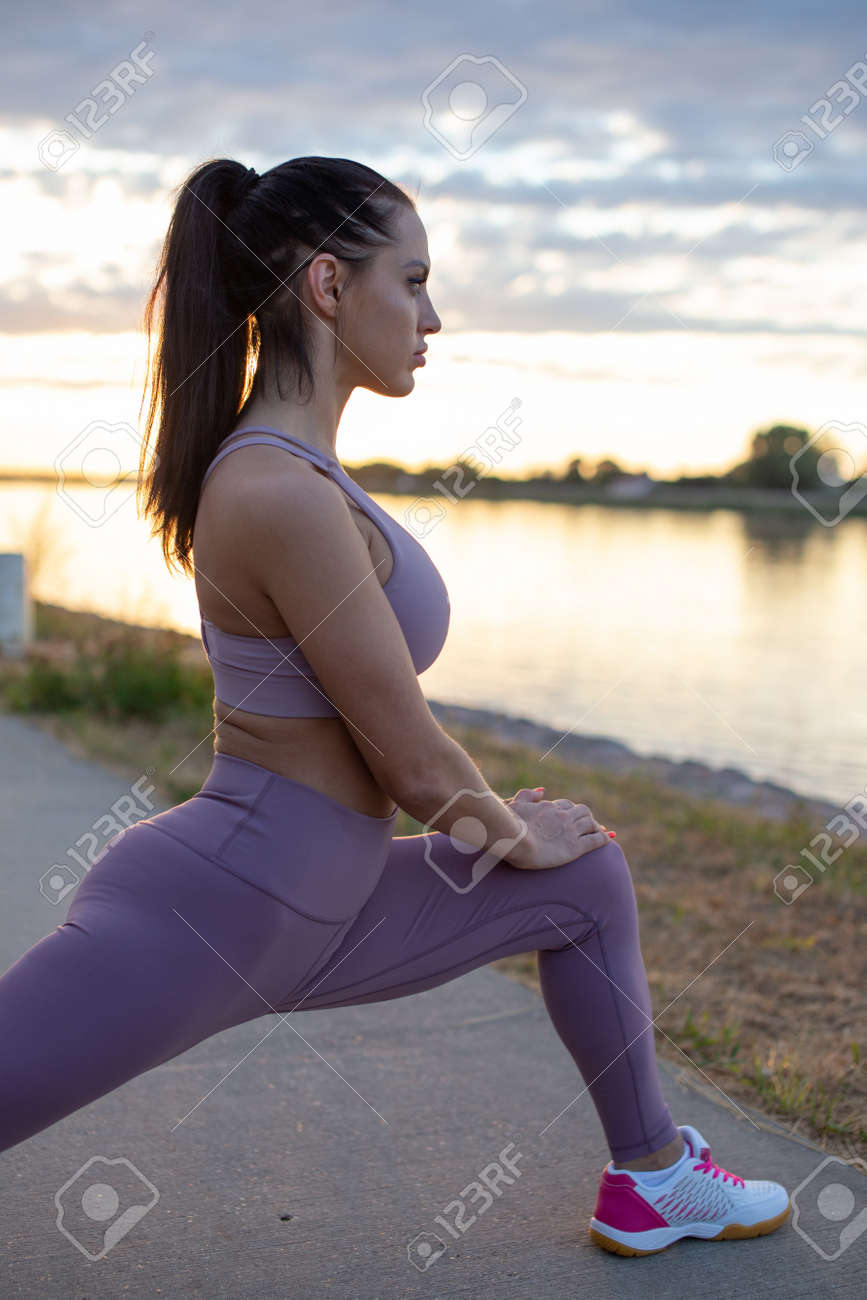 Young Caucasian woman stretching before running, warm up exercise, profile view - 172324397
