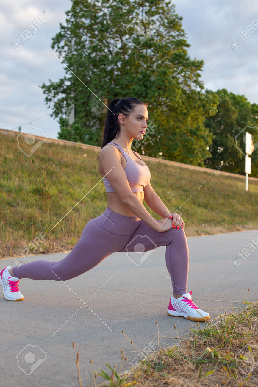 Young woman stretching before running at embankment, warm up exercise - 172324137