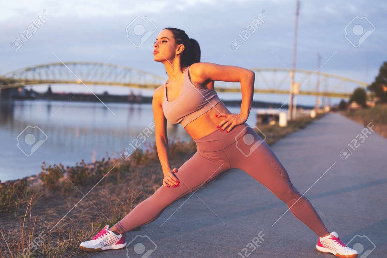 Young Caucasian jogger woman stretching legs before run at riverside - 172716052