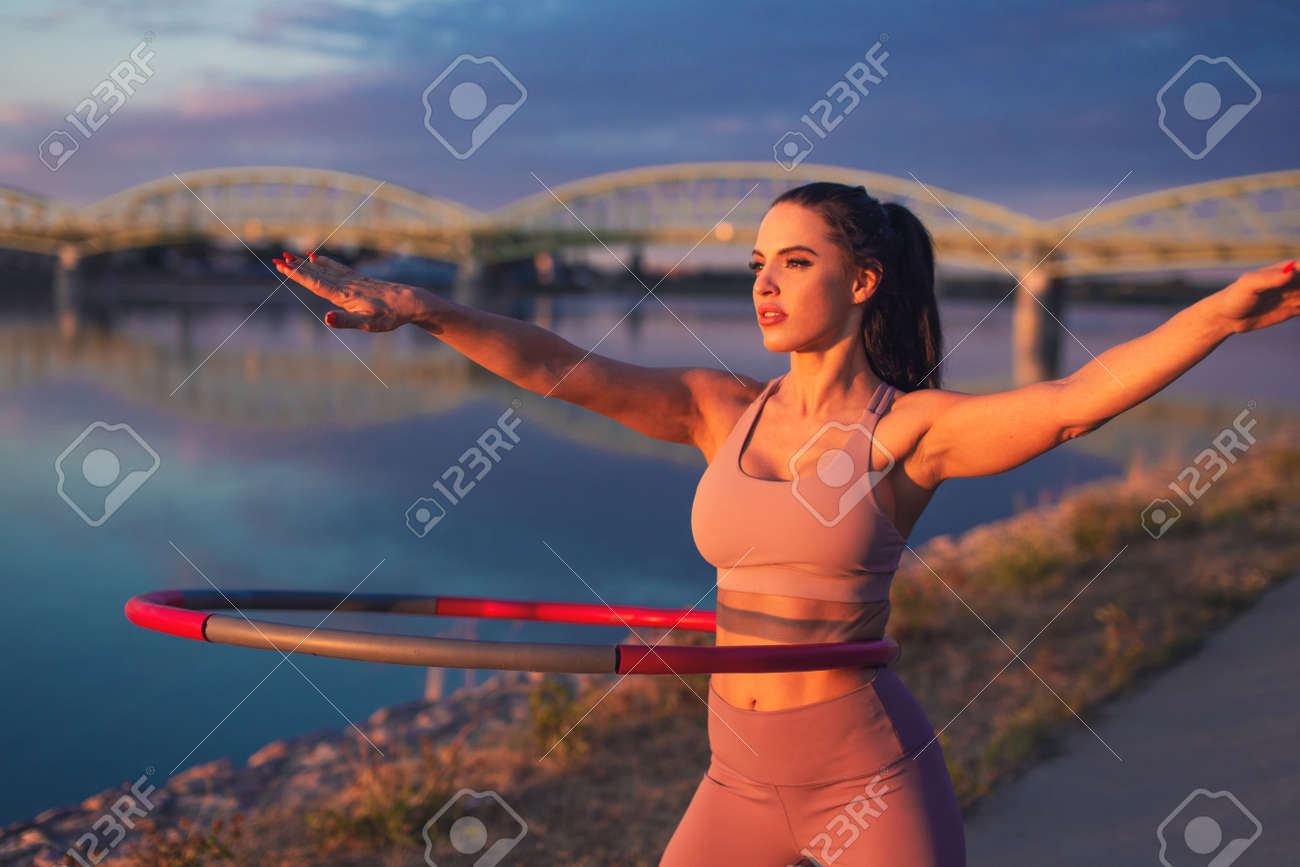 Young woman doing hoop exercise at riverside in sunset - 172863803