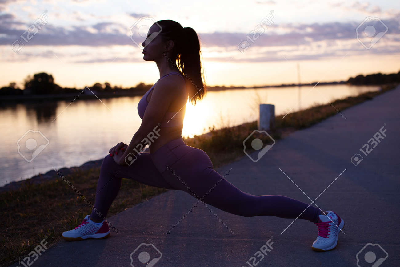 Young woman silhouette doing stretching warm-up exercise before running at morning at riverbank - 172747736