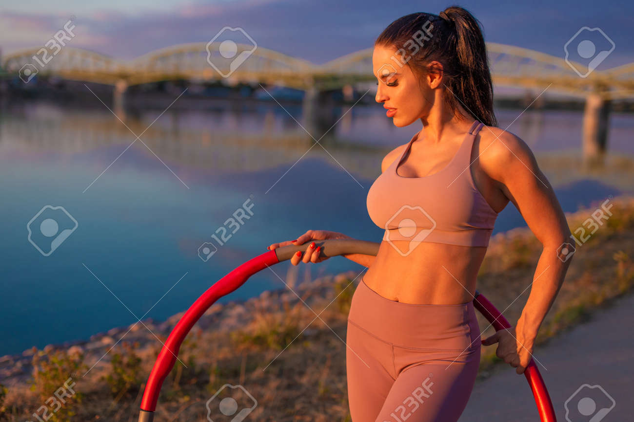 Happy young sporty woman with hoop posing at riverbank - 172863840