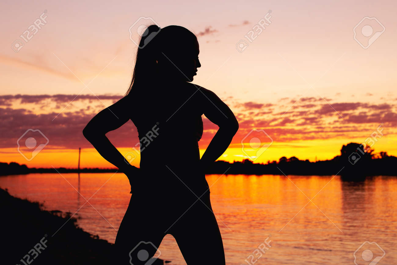 Sexy young woman silhouette in orange sunset at riverbank horizontal - 172863863
