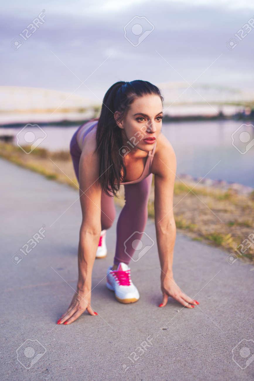 Young Caucasian sprinter woman practicing start at riverbank vertical - 172863866