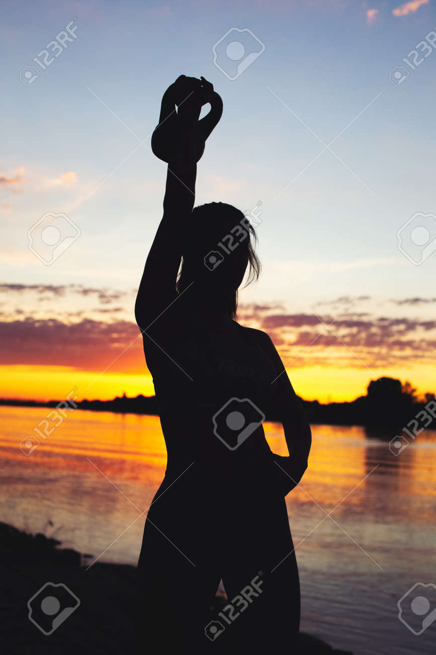 Young sporty woman silhouette holding kettlebell at riverbank - 172747243