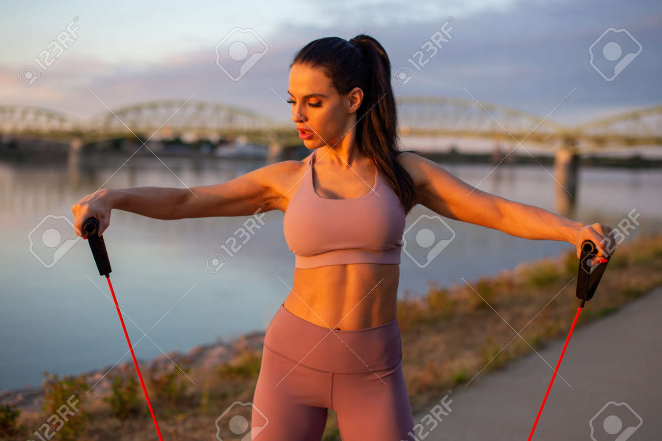 Young woman doing biceps exercise by expander at riverbank, horizontal - 172747457