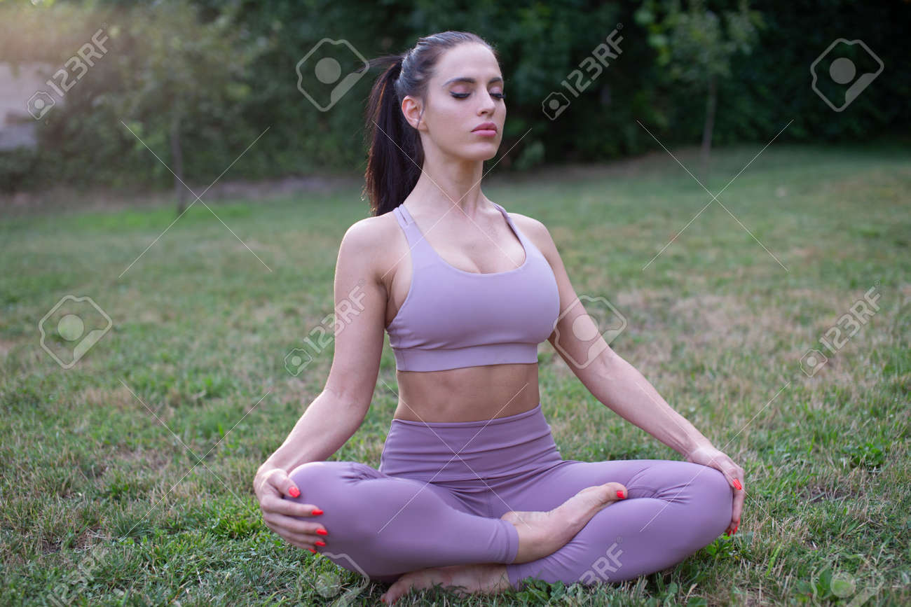 Young woman in sportswear meditating in yoga lotus sit pose outdoors in garden - 172863880