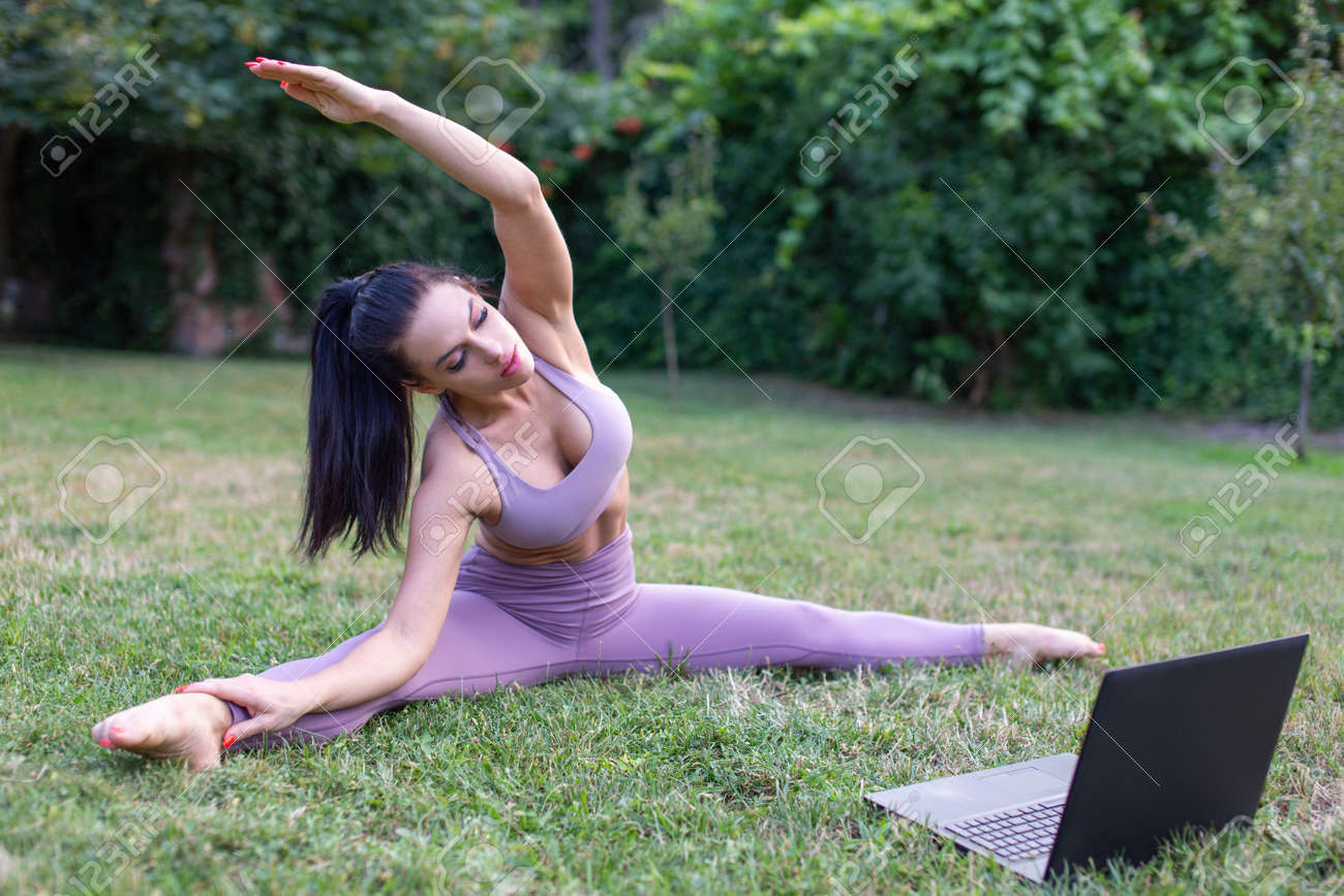 Young woman in sportswear learning from tutorial video stretching in garden, outdoors - 172852649