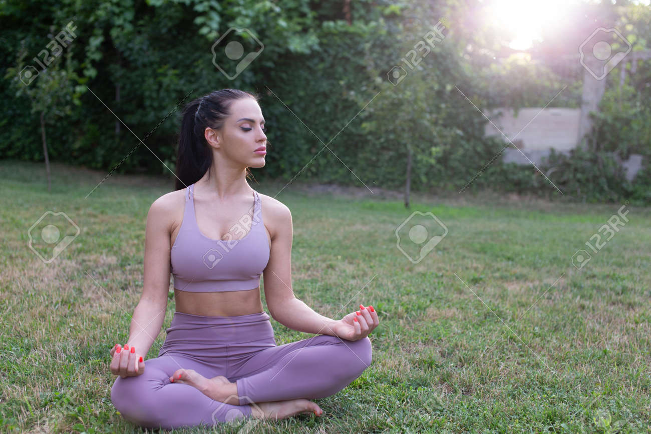 Young woman relaxing in yogla lotus pose at garden, outdoors, eyes closed - 172863890