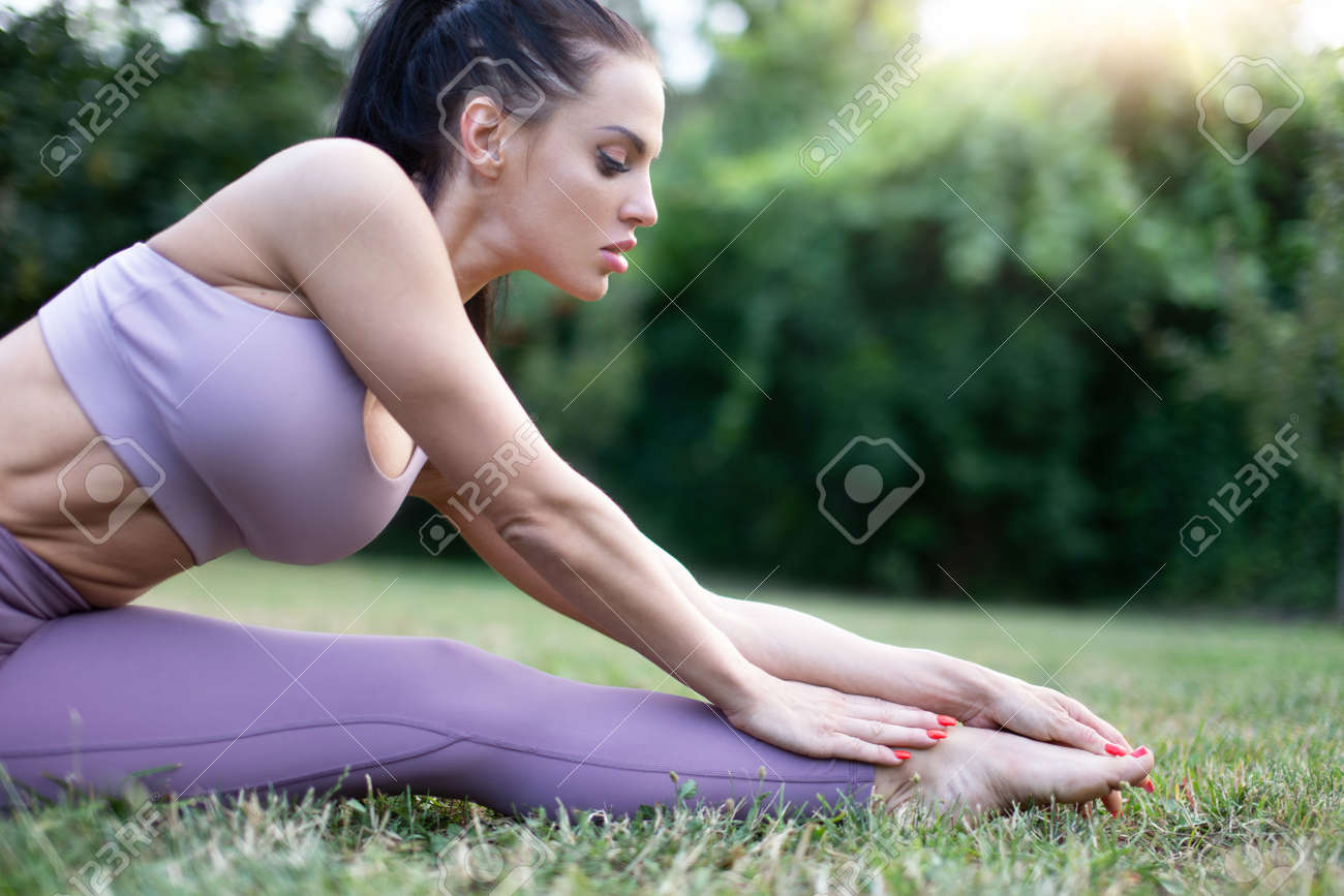 Young woman in sportswear stretching in garden on grass, outdoors, in sunset - 172852479
