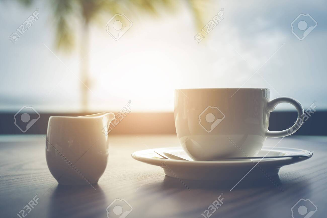 Hot coffee with milk on table in the morning time - 126556194