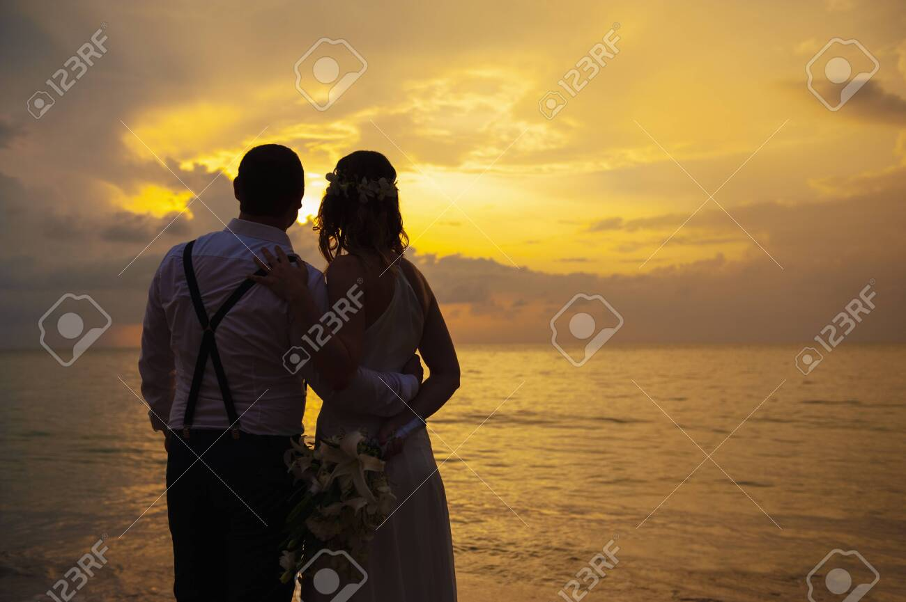 happy romantic wedding couple in love and look at the horizon with sunset - 126560018