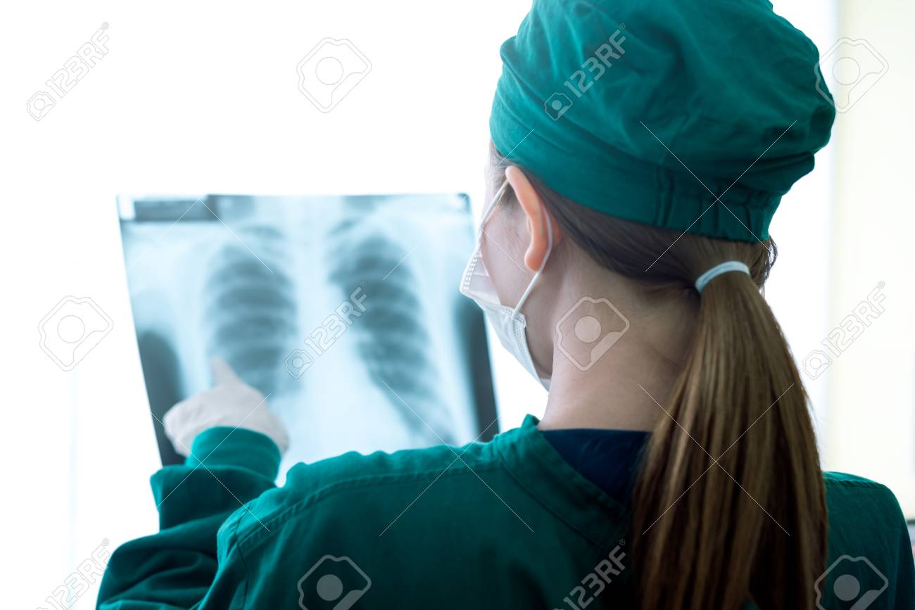 Female women medical doctor looking at x-rays in a hospital .checking chest x ray film at ward - 109003438